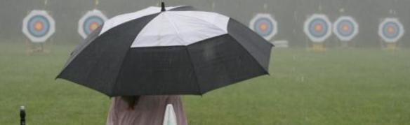 Bild von einer Bogenschützin Regenschirm vor einer Reihe von Zielscheiben, Copyright: Pfeilflug 1998 e.V. Urheber: Lara Seehofer